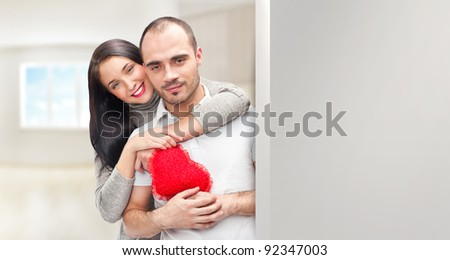 Portrait of young couple with red heart standing at their home and embracing. They are really happy to be together. Lots of copyspace for your needs - stock photo