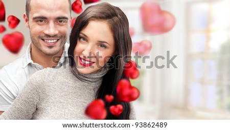 Portrait of young couple with red heart standing at their home and embracing. They are really happy to be together