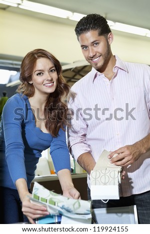 Portrait of young couple with textile samples in store