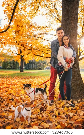 Portrait of young couple with two little dogs on walk in park on autumn day - stock photo