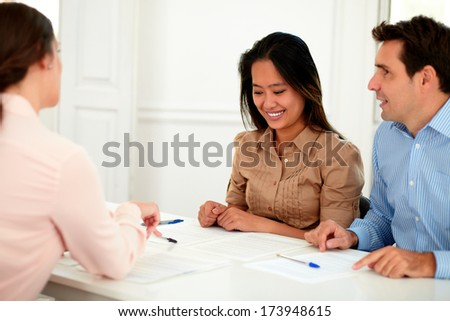 Portrait of young couple working with financial advisor while smiling and sitting on assistance workplace - stock photo