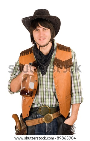 Portrait of young cowboy with a bottle of whiskey in hand - stock photo
