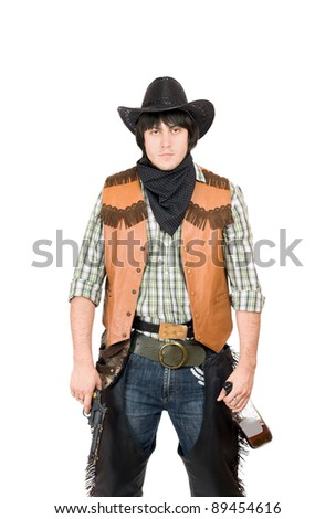 Portrait of young cowboy with a gun and bottle of whiskey in hands - stock photo