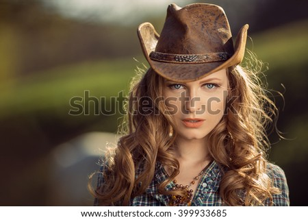 Portrait of young cowgirl outdoors. Retro style model - stock photo