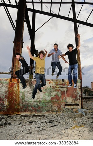 Portrait of young crazy group of male friends jumping on grunge urban scene