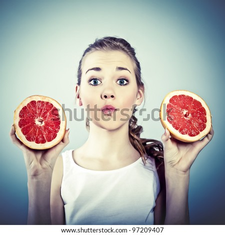portrait of young crazy woman with grapefruit - stock photo