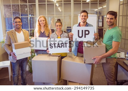 Portrait of young creative business people holding cardboard written start up - stock photo