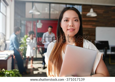 Portrait of young creative professional holding laptop in office. Young asian woman at work with colleagues discussing in background. - stock photo