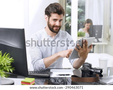 Portrait of young creative professional man sitting in his graphic design studio and holding digital tablet in his hands. Small business.