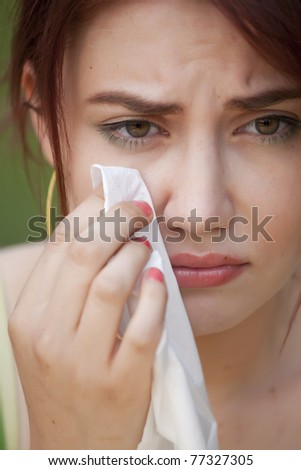 portrait of young crying woman with handkerchief - stock photo
