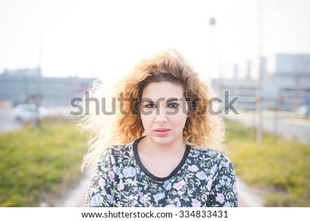 Portrait of young curly blonde hair caucasian girl posing in the street of the city, looking in camera, serious - pensive, youthful, thinking future concept - stock photo