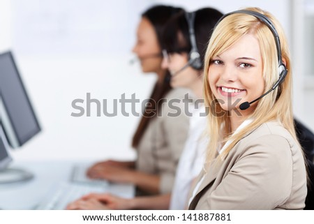 Portrait of young customer service executive wearing headset while sitting with female coworkers in background in office - stock photo