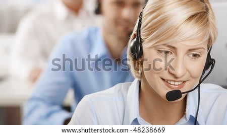 Portrait of young customer service operator talking on headset, smiling. - stock photo