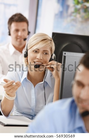 Portrait of young customer service operator talking on headset, smiling.? - stock photo