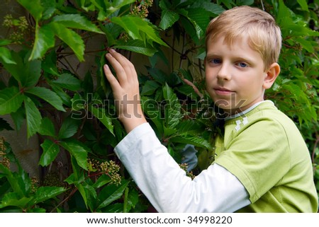 portrait of young cute boy standing outdoors - stock photo