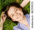 Portrait of young cute dark-haired smiling woman wearing blue blouse lying on grass at summer green park. - stock photo