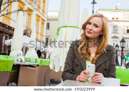 Portrait of young cute elegant woman sitting outdoor in a cafe in a city with mobile phone. She is happy