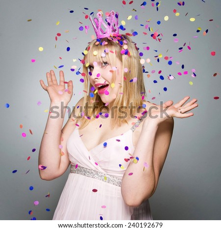 Portrait of young cute girl blowing confetti at holiday party, studio shot - stock photo