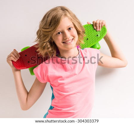 Portrait of young cute girl holding skateboard behind her head in studio against white background. - stock photo
