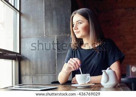 Portrait of young cute girl stirring sugar in hot tea and thoughtfully looking out of the coffee shop window while enjoying her leisure time alone. Lifestyle - stock photo