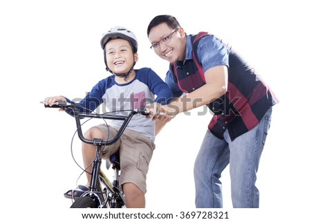 Portrait of young dad helps his son to ride a bike while holding the bike, isolated on white background - stock photo