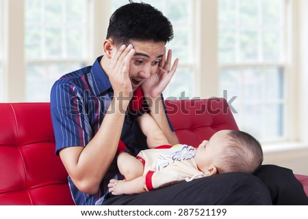 Portrait of young dad sitting on sofa at home while playing peekaboo with his baby boy - stock photo