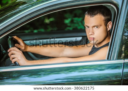 Portrait of young dark-haired handsome man driving car.