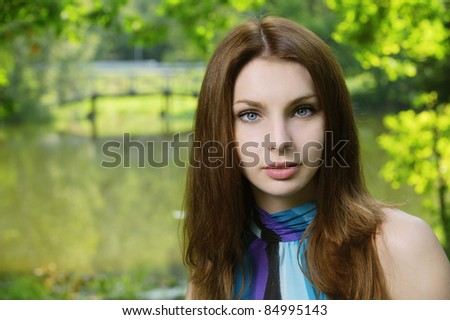 Portrait of young dark-haired pretty woman at summer green park.