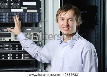 Portrait of young data center specialist in front of equipment - stock photo