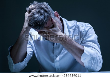 Portrait of young, depressed man in pain - stock photo