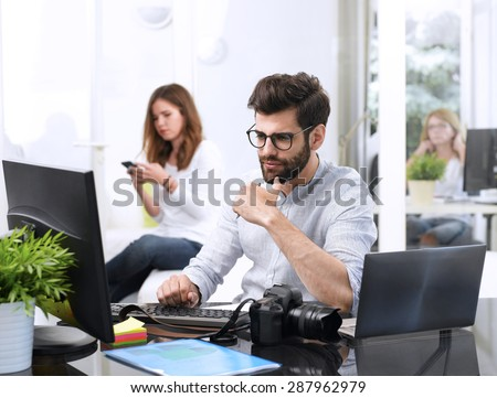 Portrait of young designer sitting at graphic studio in front of laptop and computer while working online. Assistant using her mobile at background.  - stock photo