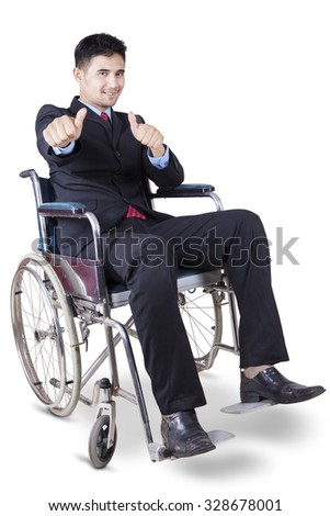 Portrait of young disabled entrepreneur smiling and showing thumbs up at the camera while sitting on the wheelchair - stock photo