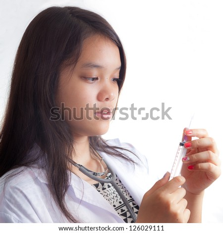 Portrait of young doctor against white background - stock photo