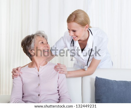 Portrait Of Young Doctor And Senior Patient Sitting On Couch - stock photo