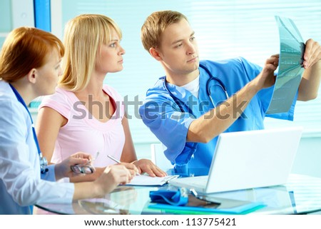 Portrait of young doctor commenting x-ray exam results to his colleague and patient - stock photo