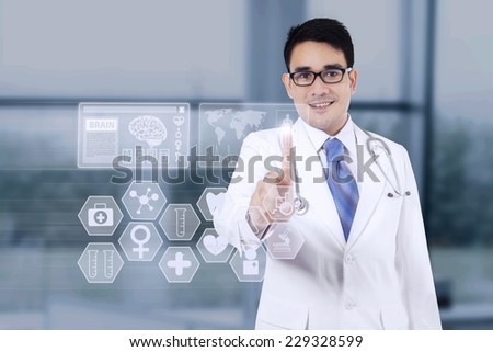 Portrait of young doctor pressing a button on the medical interface screen in the hospital - stock photo