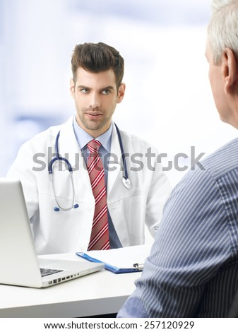 Portrait of young doctor sitting at desk with elderly patient while check up and write diagnosis.  - stock photo