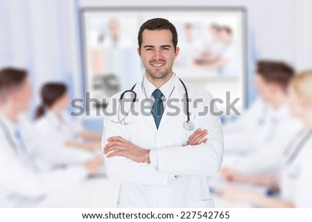 Portrait of young doctor with arms crossed against team video conferencing in meeting room - stock photo