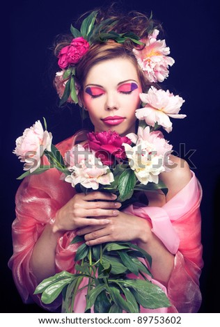Portrait of young dreaming woman with artistic make-up and with flowers in her hair