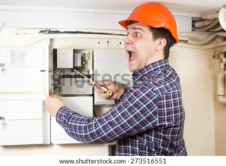 Portrait of young electrician got high voltage shock while repairing electrical system - stock photo
