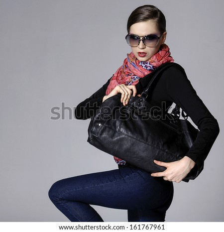 portrait of young elegant woman in the black dress with scarf posing - stock photo