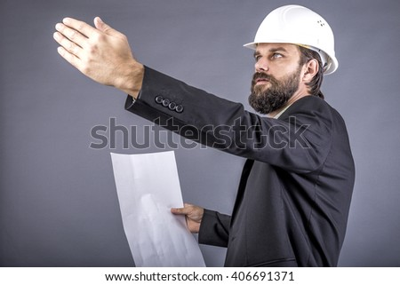Portrait of young engineer holding plan drawings and explaining something isolated on gray background - stock photo