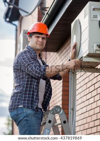 Portrait of young engineer installing air conditioner on building outer wall - stock photo