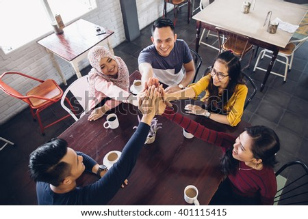 portrait of young enthusiastic team giving high five - stock photo