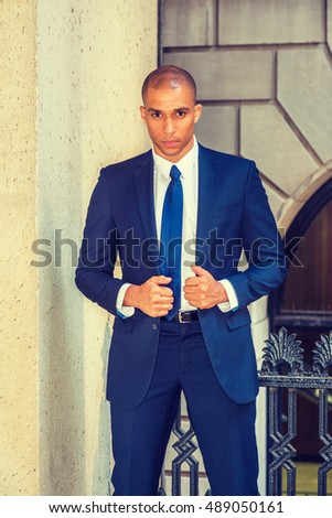 Portrait of Young European Businessman in New York. Wearing blue suit, white shirt, tie, Mixed Race French guy with shaved head stands outside office, seriously, tensely thinking. Filtered effect.