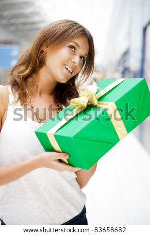 Portrait of young excited pretty woman standing inside shopping mall smiling and holding christmas gift.
