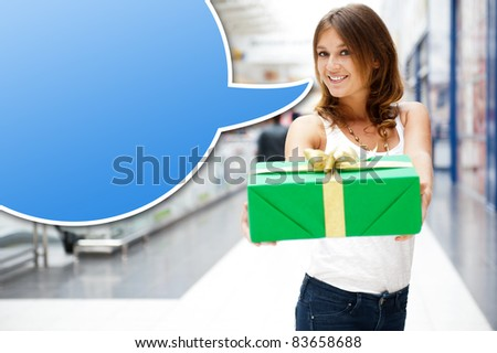 Portrait of young excited pretty woman standing inside shopping mall smiling and holding christmas gift. Blank balloon with lots of copyspace for your text and logo
