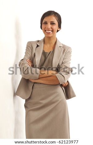 Portrait of young executive business woman wearing suit smiling with arms crossed - stock photo