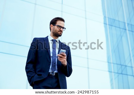 Portrait of young executive looking stressed standing near office with smart-phone in the hand - stock photo