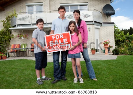 Portrait of young family holding a foreclosure sign outside their house - stock photo